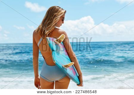 Outdoor View Of Attractive Female Model In Blue Swimsuit, Holds Her Surfboard, Stands At Beautiful O