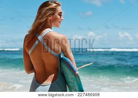 Charming Beautiful Young Female Model In Swimsuit, Stands Back, Demonstrates Her Perfect Body Or Fig