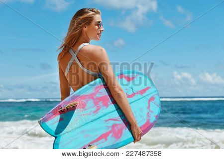 Portrait Of Professional Young Female Surfer In Sunglasses, Holds Blue Big Surf Board, Stands Near B