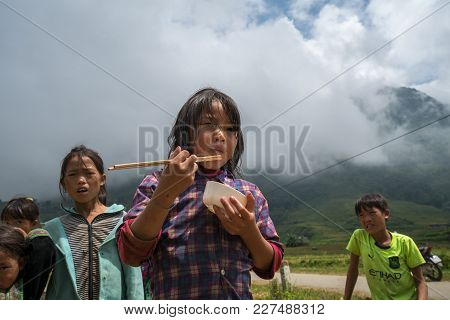 Lao Cai, Vietnam - Sep 7, 2017: Ethnic Minority Child Having Lunch With Her Family On Rice Field On