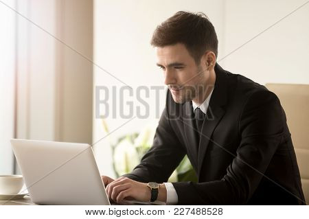Attractive Man In Business Suit Using Laptop While Sitting At Desk. Millennial Businessman Reading E