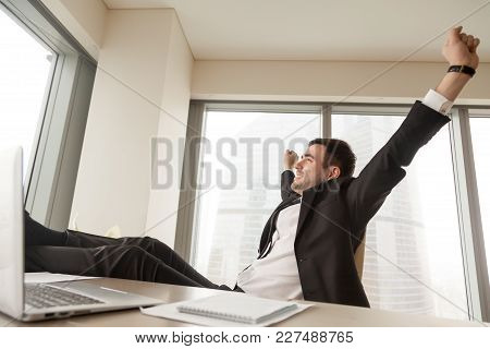 Happy Businessman Stretching While Sitting With Legs On Desk In Office. Satisfied Office Worker Rela
