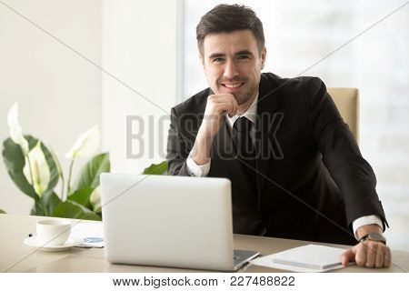 Portrait Of Happy Smiling Businessman Sitting At Work Desk In Front Of Laptop, Looking In Camera. Su