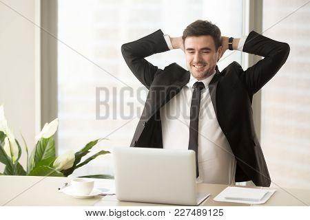 Happy Smiling Businessman Looking At Laptop Screen While Sitting At Desk With Hands Behind Head. Com