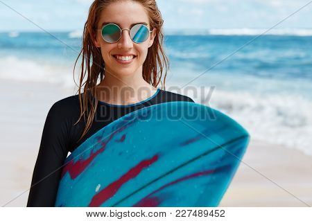 Cheerful Satisfied Female In Shades And Wet Suit, Being In Good Mood After Active Surfing On Waves W