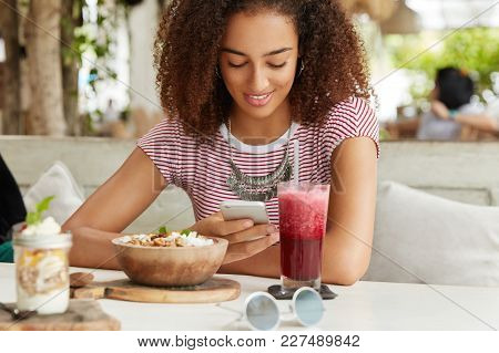 View Of Pleasant Looking Curly African American Female Texts Messages On Cell Phone, Connected To Wi