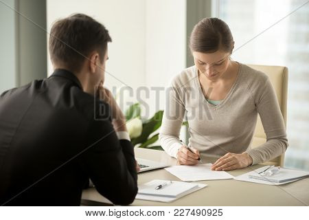 Satisfied With Loan Terms Woman Singing Contract When Sitting At Desk In Front Of Male Bank Employee