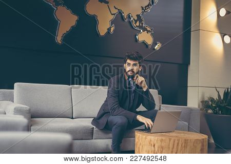 Businessman Sitting In A Modern Office, Working On A Laptop Computer; International Company Ceo Plan