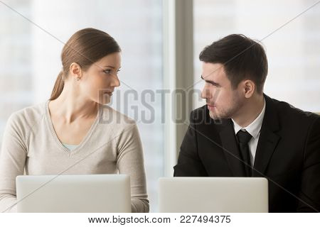 Female And Male Colleagues Carefully Looking On Each Other When Sitting At Desk. Competition In Work