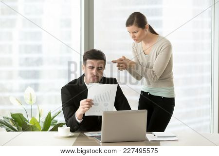 Angry Woman Aiming With Finer Gun At Head Of Her Hateful Boss Who Attentively Reading Financial Repo