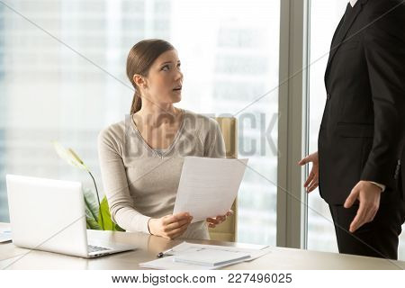 Confused Young Female Employee Listening Claims Of Head Manager On Mistakes In Business Papers, Surp