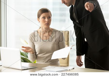 Executive Manager Giving Written Dismiss Order To Shocked Female Employee, Pointing At Door And Aski