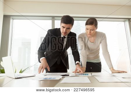 Female Customer Choosing Tint Of Blue Color On Palette For Painting Walls In House Living Room While