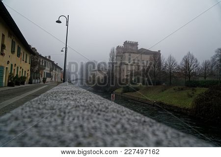 Old Arch Stone Bridge In Foggy Weather, Haze Winter In Italy.