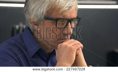 Side View Of Depressed Senior Man In Glasses