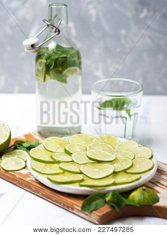 Limes slices and lemonade drink with mint and green lime on background