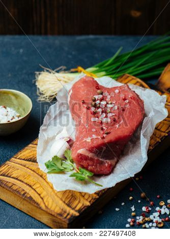 Raw beef meat on a wooden cutting board, ready for cooking. Red meat and spices