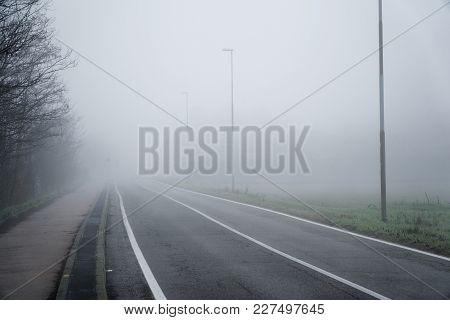Asphalt Road That Goes Through A Misty Foggy Dark Misterious Pempty Fields.