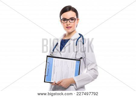 Portrait Of Young Attractive Female Doctor In White Coat Standing In Office And Looking In Camera Co