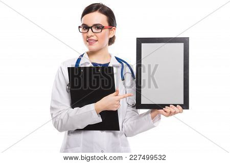 Portrait Of Young Attractive Female Doctor In White Coat Standing In Office Smiling Looking In Camer