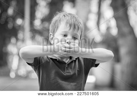 Serious Little Caucasian Boy Closing Mouth With Hands. Asperger Syndrome, Autistic Child, Autism, Re