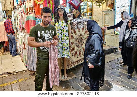 Tehran, Iran - April 29, 2017: An Iranian Man Stands Near A Textile Store In The Grand Bazaar Of Teh