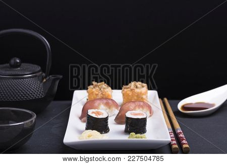 We See In The Image A Mix Of Sushi In A White Porcelain Tray, Next To It We See Some Chopstickes, Th