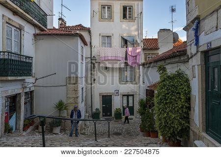 Lisbon, Portugal - October 22, 2017: Street Scene In A Narrow Street Of The Historic Neighborhood Of