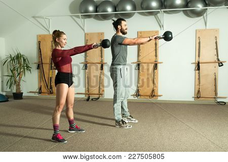 Young Couple Kettle Bell Fitness Exercise In The Gym, Selective Focus
