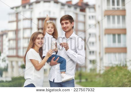 Cute Little Girl Smiling Showing Thumbs Up Her Parents Holding Keys To Their New Home In Apartment B