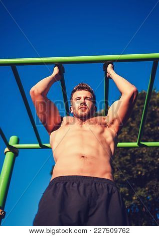 Young Sportsman Build Man Doing Pull Ups Exercises Outdoors In Sunny Day