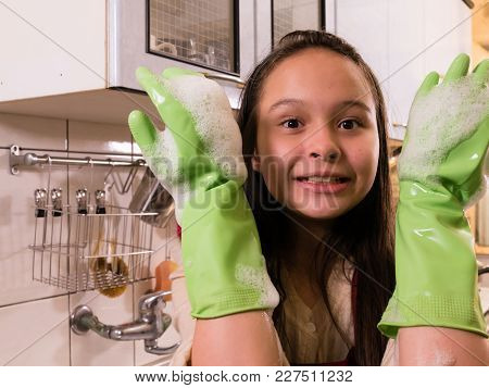 Asian  American Girl Washing Dishes With Funny Expression