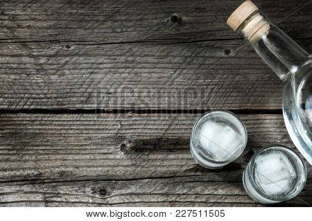 Two Shot Glasses With Cold Vodka Or Gin On Wooden Table,