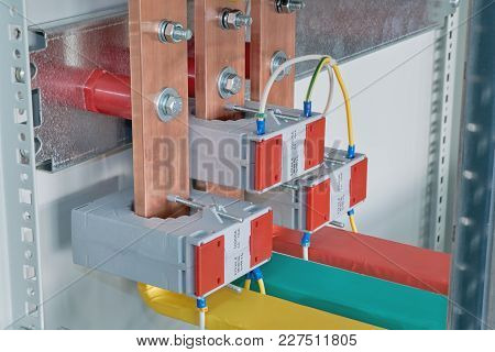 Copper Busbars With Current Transformers On Them In An Electric Cabinet. Copper Busbars Are Bolted T