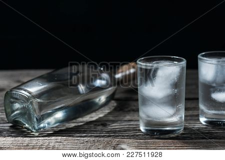 Vodka In Shot Glassesand Bottle On Rustic Wood Table Black Background