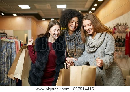 Women Of Diverse Ethnicity With Shopping Bags Posing In Clothing Store. Portrait Of Three Smiling Mu