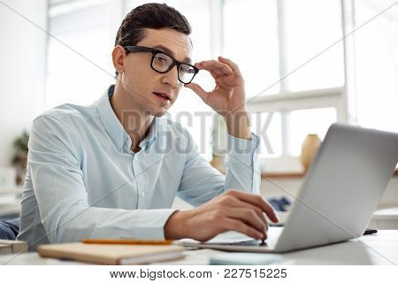 Working. Handsome Concentrated Dark-haired Man Working On His Laptop And Touching His Glasses While