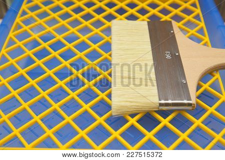 Repair, Redecorating Concept. A Wooden Paint Brush On A Blue Plastic Pan With A Yellow Grid, Close U