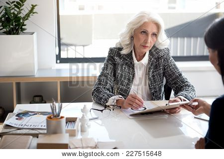 Demanding Boss. Confident Serious Old Woman Is Holding Documents With Pen And Looking At Her Worker