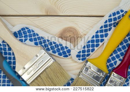 Repair, Redecorating Concept. A Pair Of Protective Work Gloves And Paint Brushes On A Light Uncolore