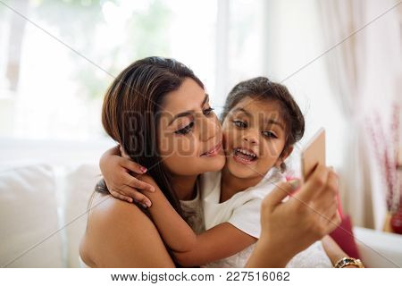Young Indian Woman Taking Selfie With Her Adorable Little Daughter