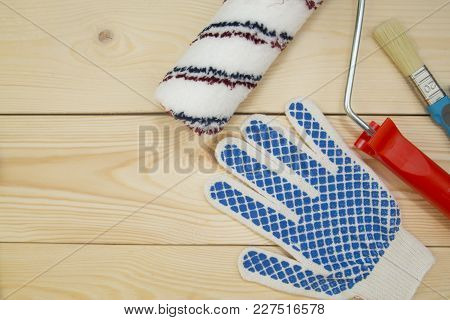 Repair, Redecorating Concept. A Paint Roller, A Brush And A Protective Glove On A Light Uncolored Wo
