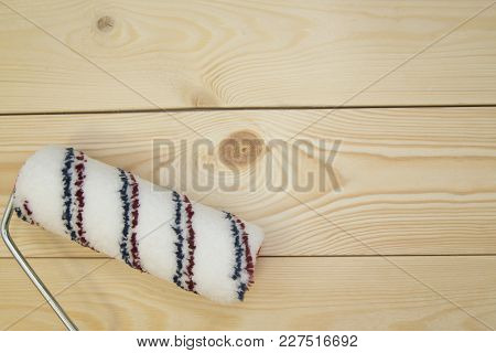 Repair, Redecorating Concept. A Paint Roller On A Light Uncolored Wooden Background With Copy Space,