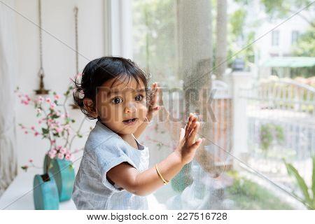 Adorable Curious Indian Baby Girl At Big Window