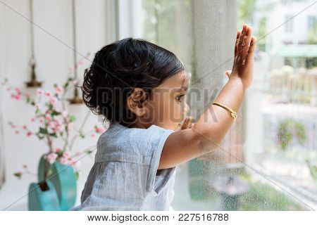 Curious Little Kid Looking At Something Interesting Through The Window
