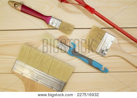 Repair, Redecorating Concept. A Set Of Wooden And Plastic New Paint Brushes And A Concrete Mixer On