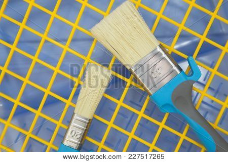 Repair, Redecorating Concept. Paint Brushes And A Paint Roller On A Blue Plastic Pan With A Yellow G