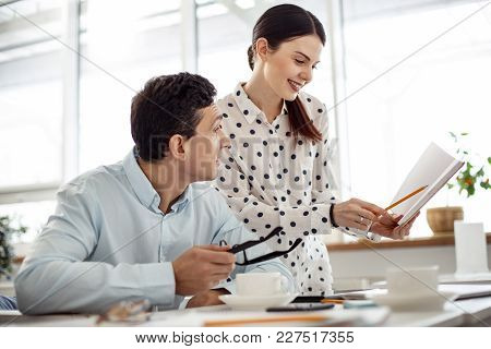 Co-workers. Beautiful Happy Dark-haired Young Woman Smiling And Showing Her Notebook To A Man Sittin