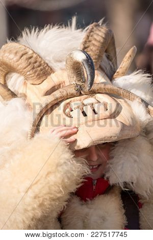 Pernik, Bulgaria - January 26, 2018: Young Boy Smiles While Lifting Up His Scary Kuker Wood And Fur