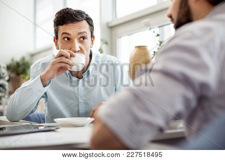 Negotiating. Attractive Concentrated Dark-eyed Man Talking With His Partner Sitting Next To Him And